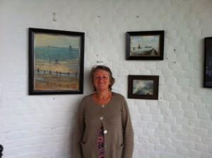 Vuurtorenbeheerder Sue Daish tussen drie werken van Piet Mulder