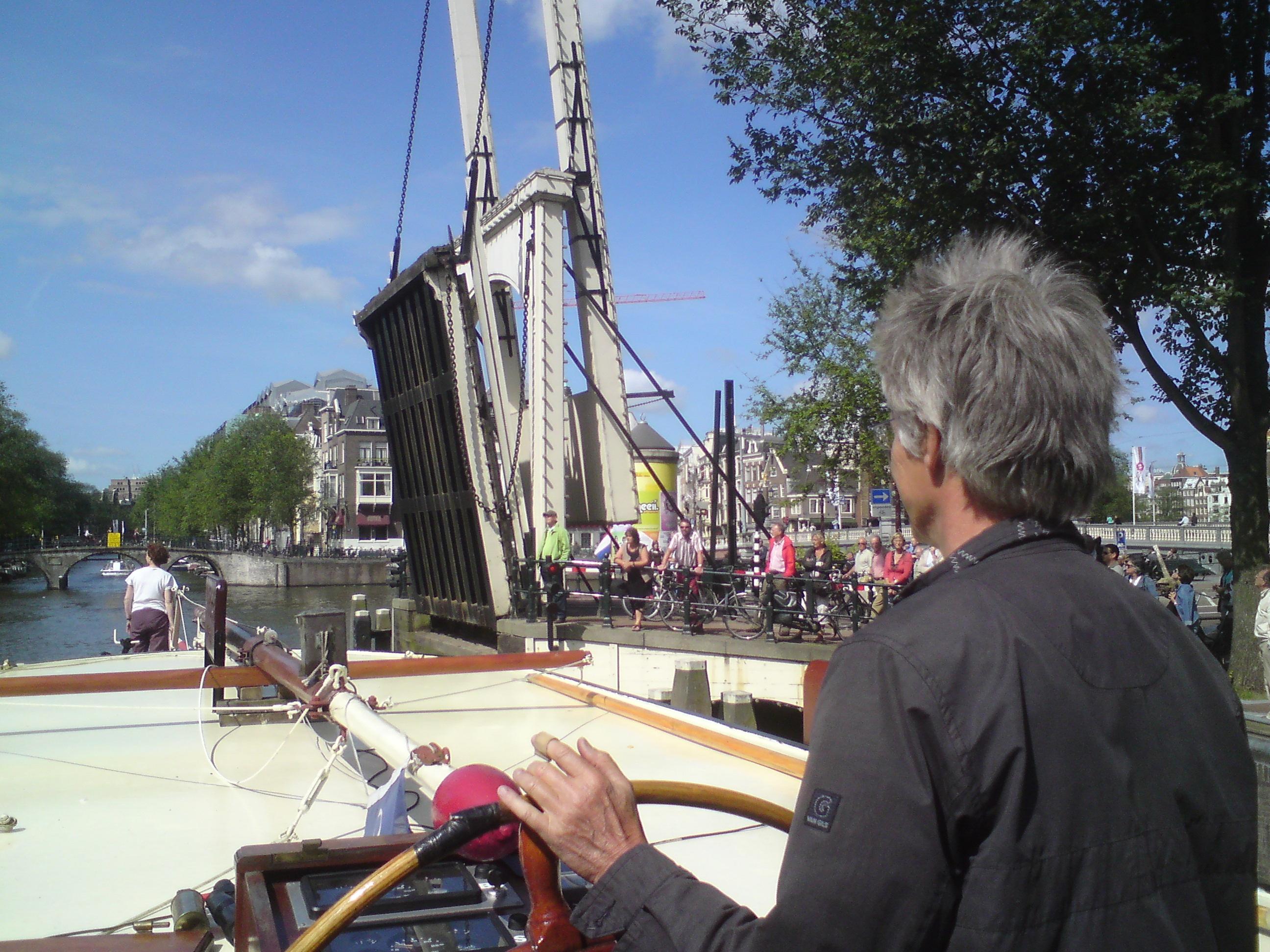 Dick Pels stuurt zijn kruiser door de Nieuwe Herengracht. Voor op het dek zijn vrouw Baukje Prins.